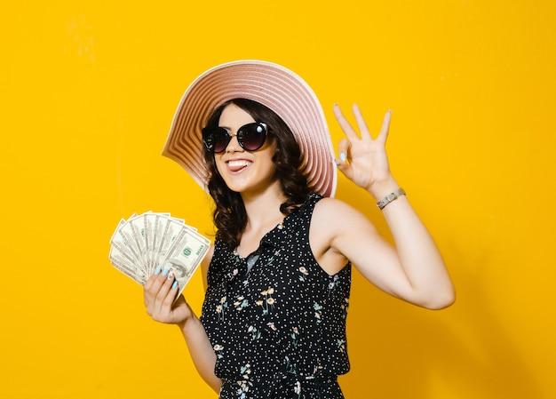 Портрет жизнерадостной молодой женщины с солнечными очками и шляпой держа банкноты денег и празднуя изолированный над желтой стеной