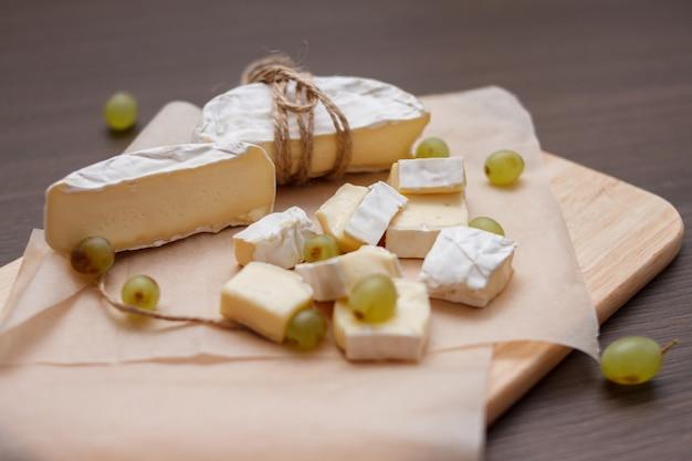カマンベールチーズとまな板の上の緑のブドウをクローズアップ