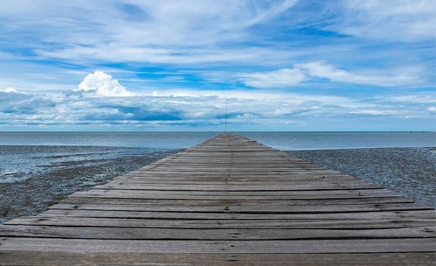 海と青い空の長い木製の通路の端