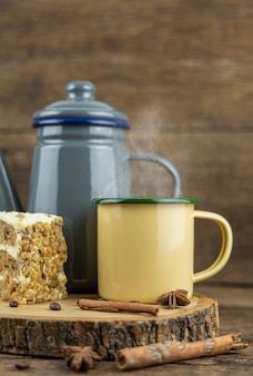お茶のポットと木製のテーブルにケーキと熱いお茶の黄色のブリキのカップ。