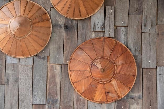 竹製の帽子とヤシの葉が木製の壁に掛かる