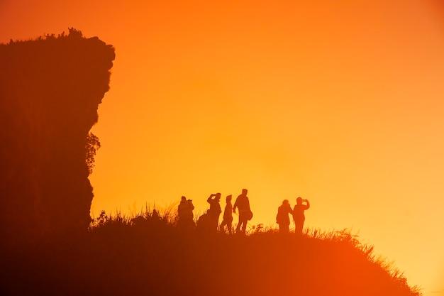 日の出を待っている暗闇の中で丘の上に非常に多くの人々のシルエット。