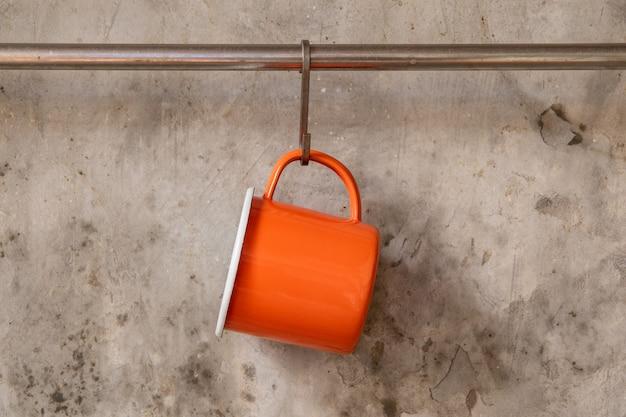 セメントの壁にステンレスレールに掛かっているオレンジ色の錫カップ