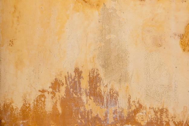 明るい茶色のセメント色の古い壁の背景。