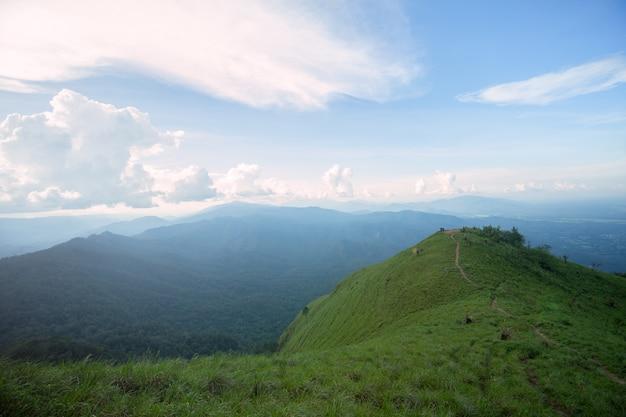 山の上に芝生のフィールドを通して日光