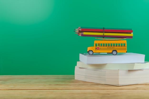 学校に戻る 。テーブルの上の色鉛筆とスクールバス