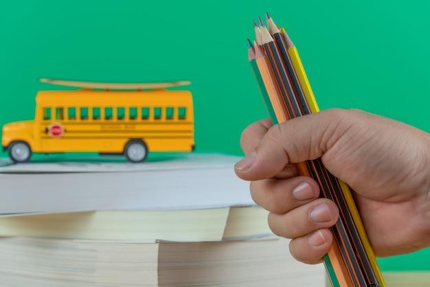 学校に戻る 。スクールバスと本を持つ手マンの色鉛筆