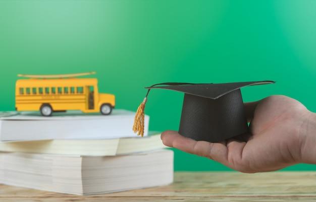 学校に戻る 。スクールバスと本を持つ男を手に卒業キャップ