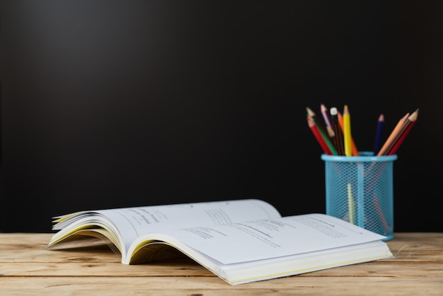 学校に戻る 。ホルダーに色鉛筆でテーブルの上の本