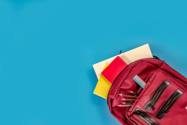 Обратно в школу . школьная сумка и принадлежности на синем