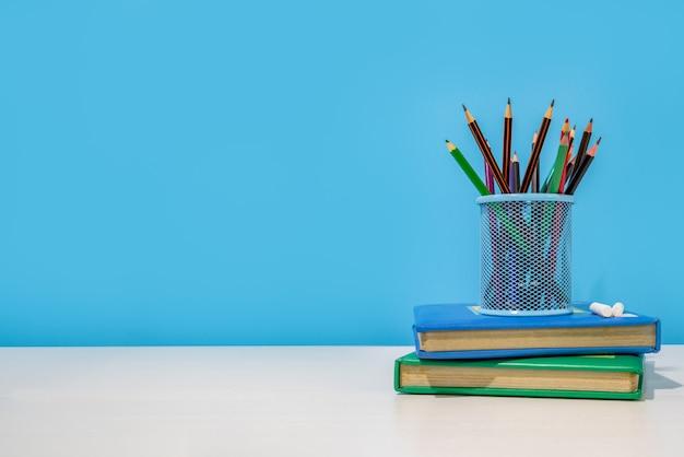 教育コンセプト。鉛筆ホルダーと白いテーブルの上の本の鉛筆