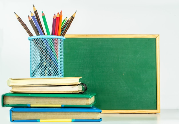 教育コンセプト。鉛筆ホルダーと白いテーブルの上の本の色鉛筆