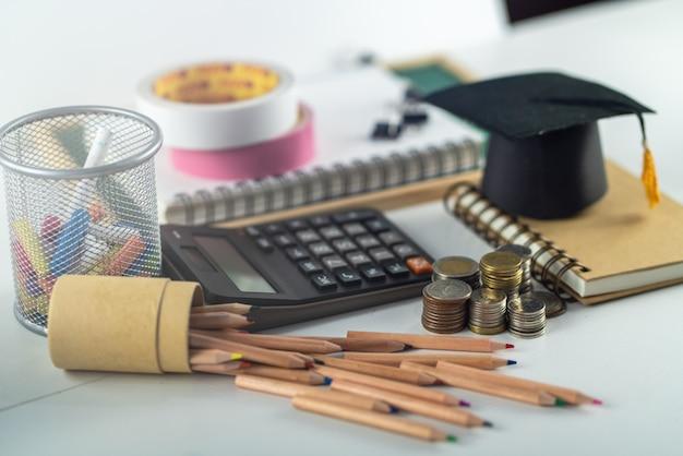 Концепция образования деньги монеты и калькулятор со школьными принадлежностями на белом столе