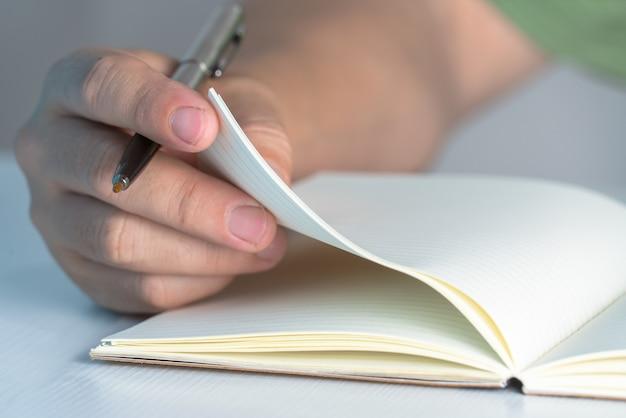 Концепция образования рука человек пишет тетрадь на столе