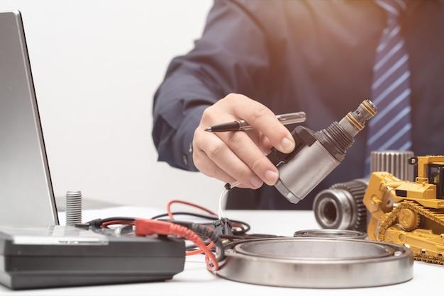 プロのエンジニアがオフィスでの作業中にソレノイドバルブに手を伸ばして、修理メンテナンス重機コンセプト