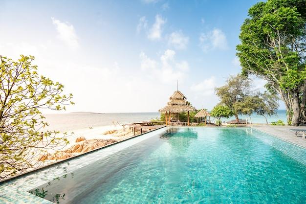 Бассейн над прекрасным видом на море на райском пляже, отдых летом