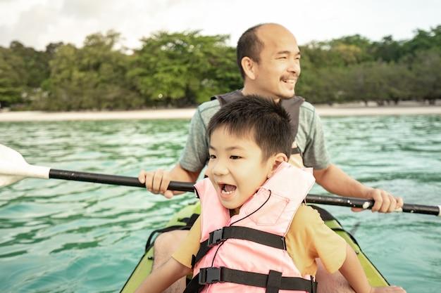 Мужчины и шильды на каяках в море, летние каникулы для детей