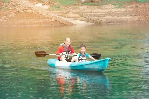 Мужчины и шильд на байдарках по реке, летний отдых для детей