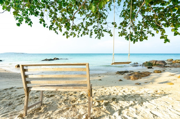 Стул и гамак на пляже в летние каникулы, райский пляж с синим морем и небом