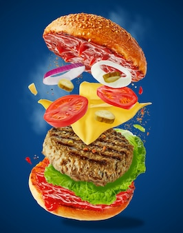 Большой вкусный домашний бургер с летающими ингредиентами на синем фоне