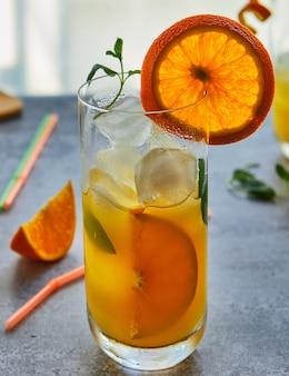 ガラスの瓶に新鮮なオレンジジュースの写真。夏の健康的な有機飲料のコンセプト。