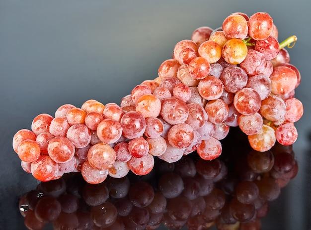 灰色の背景に水滴と新鮮な赤ブドウ
