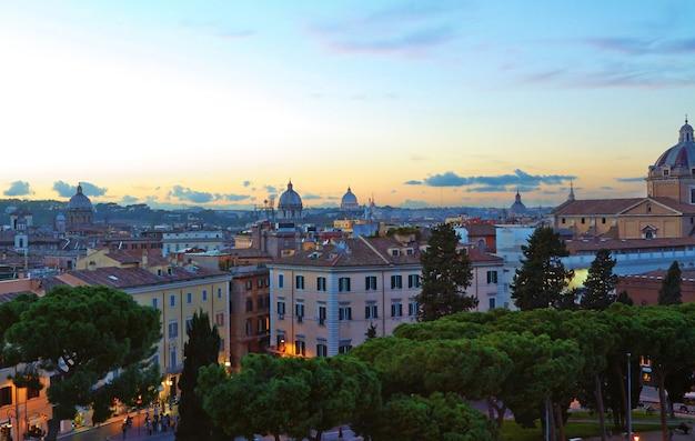 ローマのパノラマの建物の夜、夕暮れ時のイタリアの古代建築とローマの屋上ビュー
