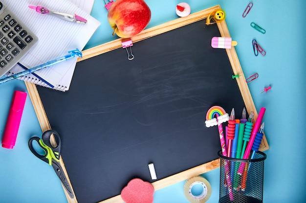 教室の鉛筆、ノート、本、はさみのアクセサリーと学校の背景に戻る