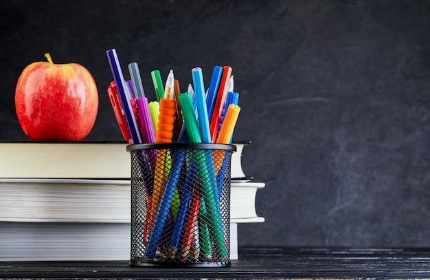 コピースペースと黒板に本とリンゴと学校の背景に戻る