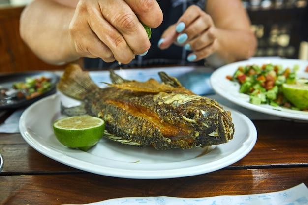 レモンを保持し、プレートスレーブレストランに揚げ魚を注ぐ女性の手。