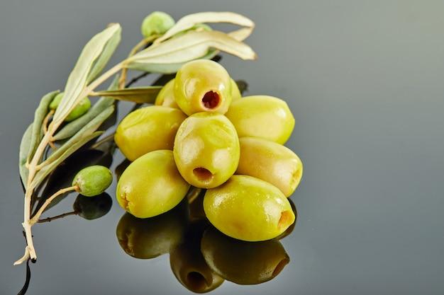 Оливки с веткой оливкового дерева с плодами лежат в горке на сером фоне