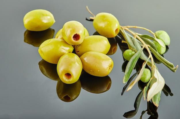灰色の背景のスライドに横たわっている果物とオリーブの木の枝とオリーブ