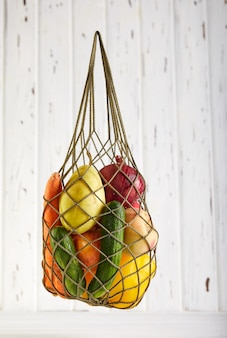 コピースペースを持つ白の有機エコ野菜と買い物袋をメッシュします。