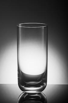 バックライト付きの灰色の背景に飲み物用のガラス