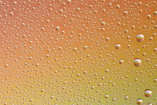 Капли на стекле разных размеров и цветов на цветном фоне, фактура