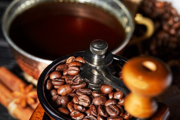 コーヒー豆と灰色のコーヒーカップと古い手動コーヒーグラインダー。コーヒー