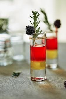 冷凍ブラックベリーの飾りとローズマリーの小枝のショットでパイナップルブラックベリーカクテル