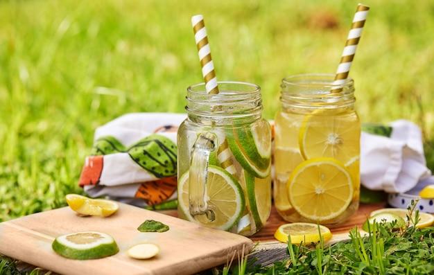 木製のスタンドにストロー付きの特別な瓶にレモンとライムを入れた爽やかなドリンク。朝は緑の芝生で撮影。健康的な食事のコンセプト