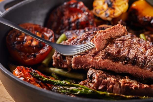 Стейк из говядины на гриле в черной сковороде, нарезанный кусочек на вилке, с запеченными овощами - помидорами, спаржей, чесноком и перцем