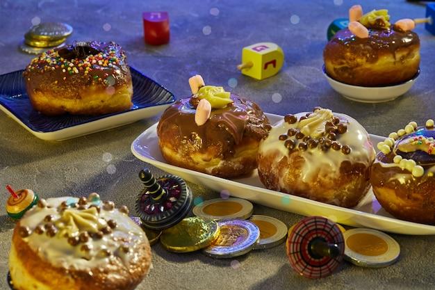 ユダヤ人の祝日のハヌカ。伝統的な料理は甘いドーナツです。青色の背景に回転するコマと、休日に子供に配るのが一般的なハヌカのお金のゲル