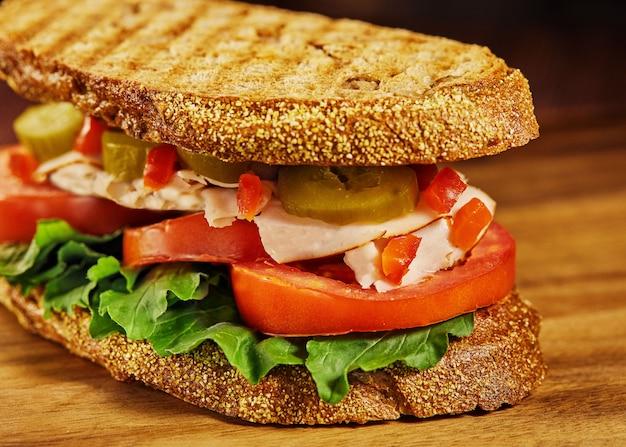 トーストした素朴なパン、新鮮なハーブ、トマトパストラミ、ピクルスのサンドイッチ。健康的な食事のコンセプト