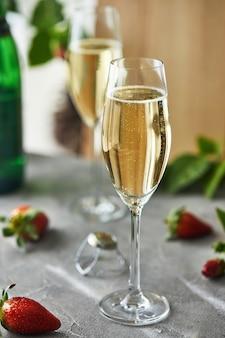 Бокалы с шампанским и клубникой на столе