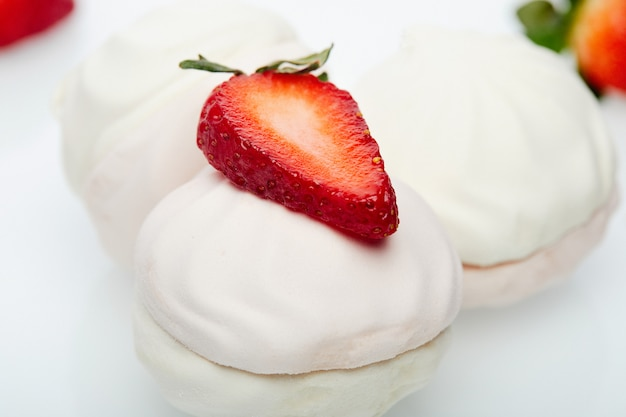 Белый зефир со свежей клубникой на белой тарелке