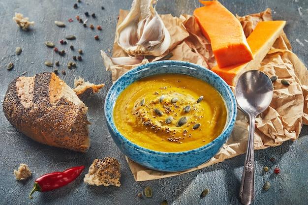 Апельсиновый суп в синей тарелке с тыквенными семечками и зернами чиа