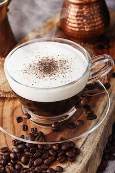 カプチーノはエスプレッソベースのコーヒー飲料で、透明なガラスのコップでコーヒーから作られた蒸しミルクの泡です。蒸気でホットコーヒー
