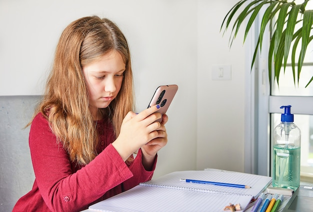 Дистанционное обучение онлайн-образование. школьница учится на дому с ноутбуком и делать школьные домашние задания. просмотр задачи в мобильном телефоне.