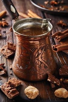 Турок с деревянной ручкой с какао крупным планом на деревянном столе, шоколад и корица, праздничная кофейня