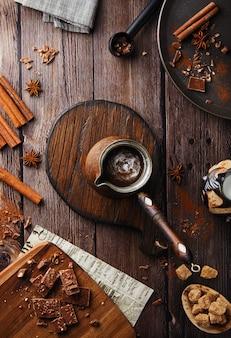 Квартира заложить какао на деревенском фоне. женская рука держит турку с деревянной ручкой из какао, шоколад с горячим напитком на деревянном столе, шоколад и корица, праздничная кофейня