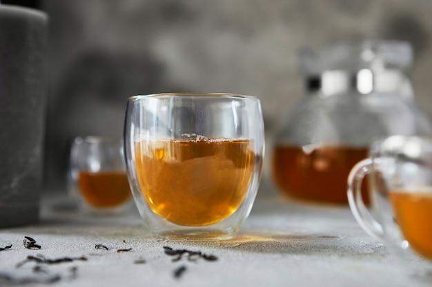 Чашки с чаем и чайник на сером фоне. крупный план. копировать пространство