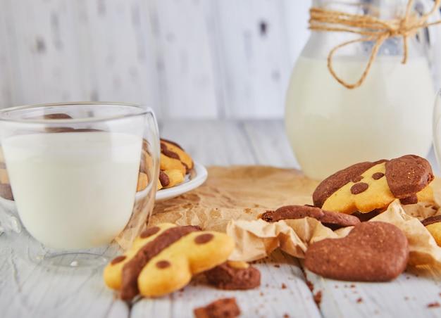 牛乳の入った犬や蝶の形をしたシンプルな自家製ショートブレッドクッキー